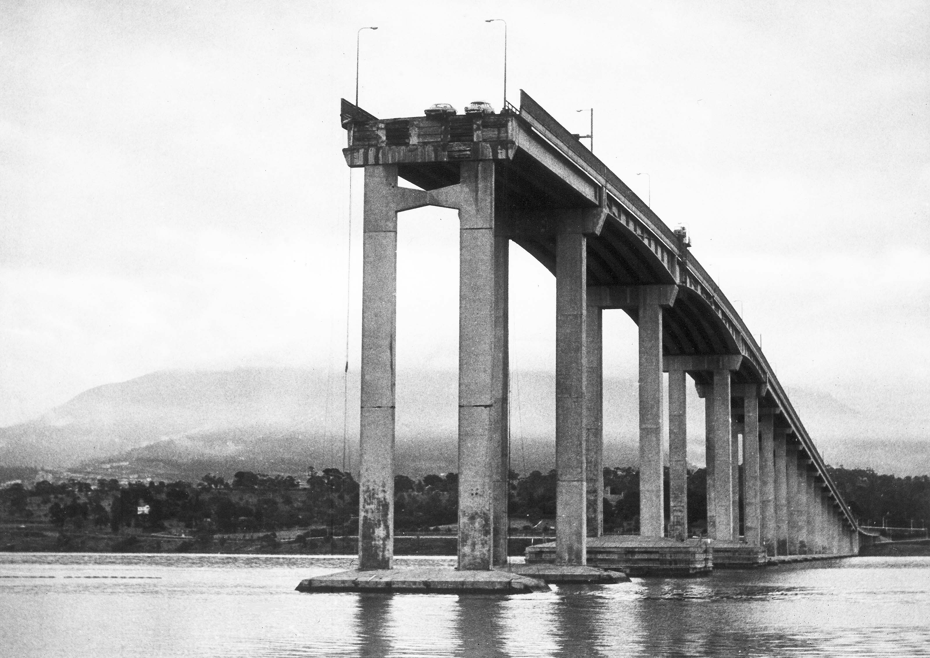 Two cars hang over the edge of the Tasman Bridge, Hobart, Tasmania, Jan. 6, 1975, after it had been rammed by Lake Illawarra, bulk ore carrier the previous evening. Four cars plunged into the River Derwent after 240-feet span of the bridge collapsed onto the deck of the carrier, sinking the ship within minutes. Five motorists and seven crewmen were killed in the collision. (AP Photo)